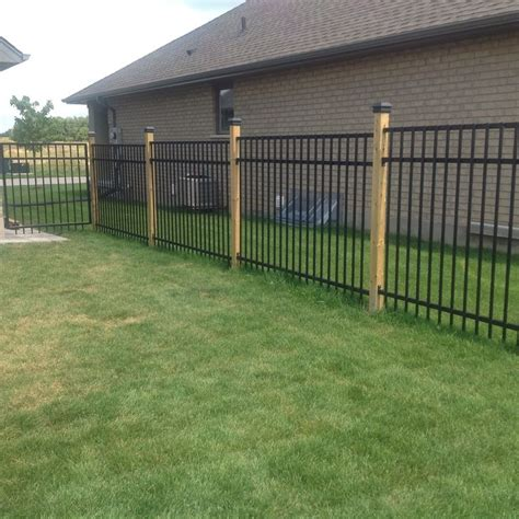 Wrought iron fence with 4x4 wood posts, black caps